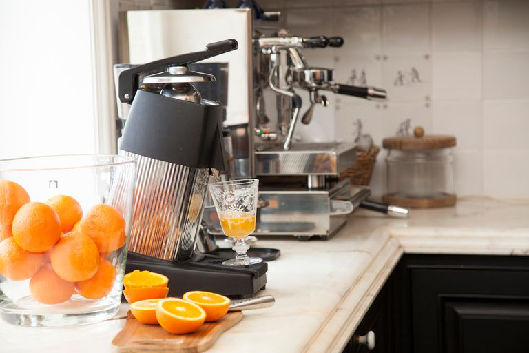 Freshly cut oranges being used to make orange juice and an espresso machine in the background.