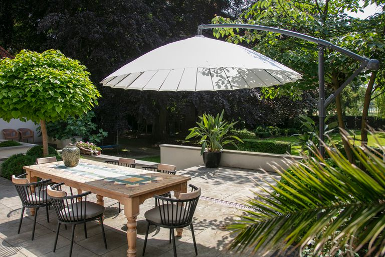 Seating area in the garden (for 6 people) and a large umbrella positioned over the table.